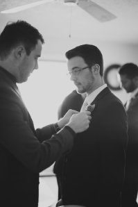 My sons- groom adjusting groomsman's boutonniere